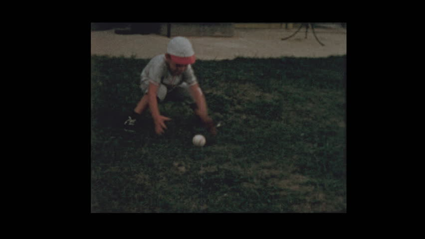 1956 young Boy catches and throws baseball in baseball uniform