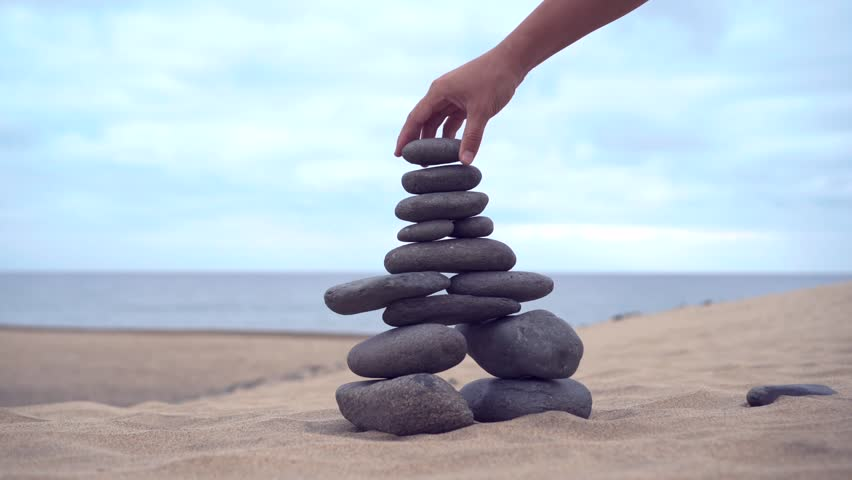 The cairn stands on the sand. The hand adds the last stone to finish the cairn. Slow motion | Shutterstock HD Video #1023013348