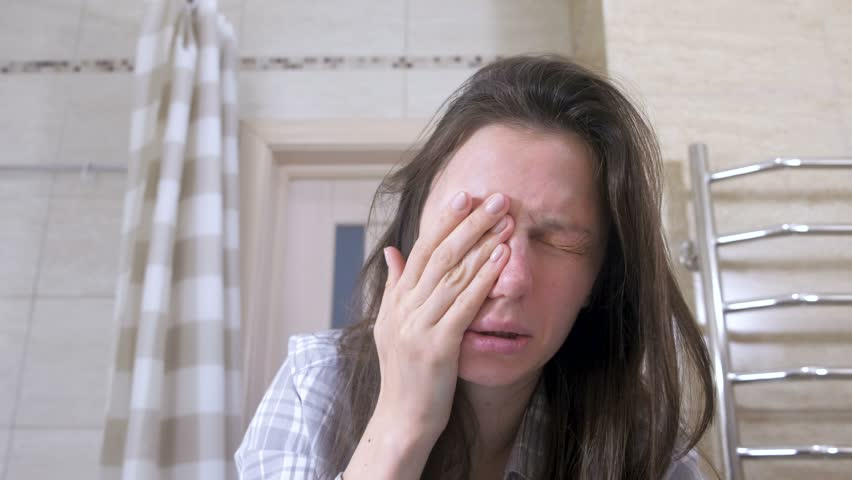 Woken tired woman in the bathroom smacks herself on the cheeks to Wake up. | Shutterstock HD Video #1023028288