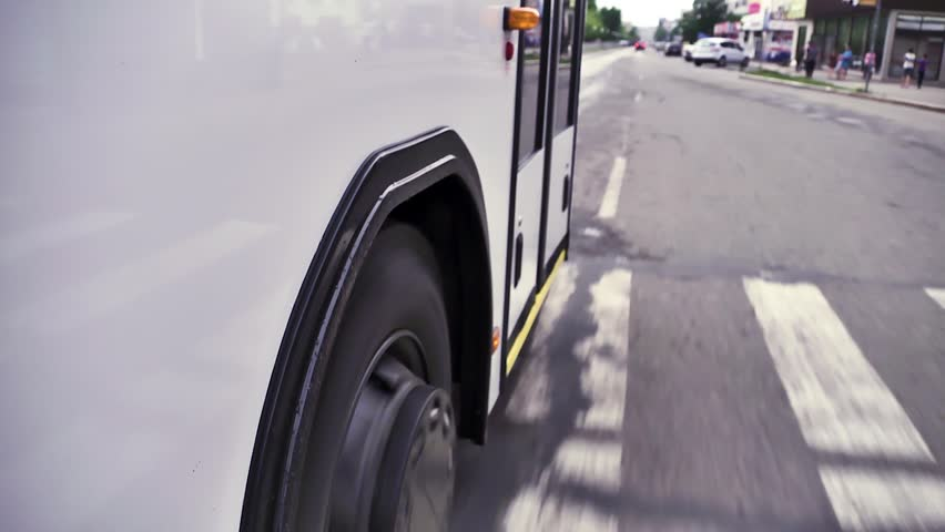 Close up view from the wheels and tires on the road of a bus riding around town. Scene. White bus moves down the street in the center of the city.   Shutterstock HD Video #1023055168