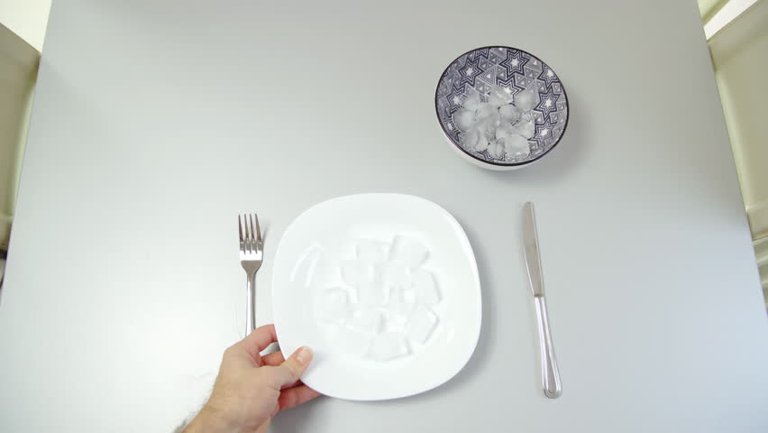 Put a plate with ice cubes on table to eat healthy sugar free vegan dinner 4K. | Shutterstock HD Video #1023081178