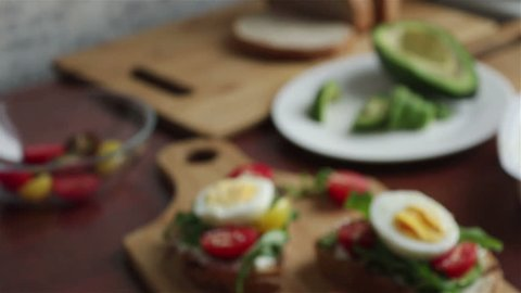bruschettas with  avocado cherry tomatoes boiling egg arugula panning shot