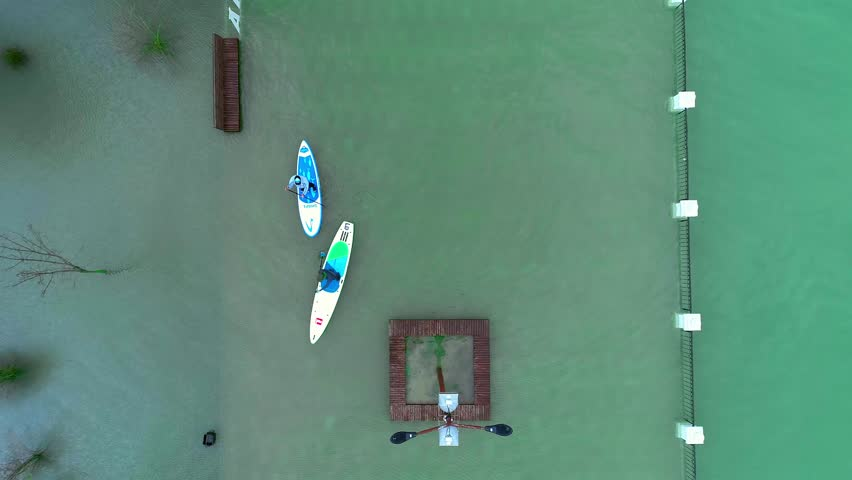 ANAPA RUSSIA - 19.01.2019: Two riders float on the sup surfboards. Swim among the trees in the old flooded park. Learning to Surf. SUP | Shutterstock HD Video #1023142798