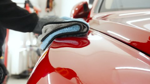 Professional car washer in black gloves wipes the car after washing and lining ceramics. Concepts of: Professional work, Various washing tools, Cleaning to shine.