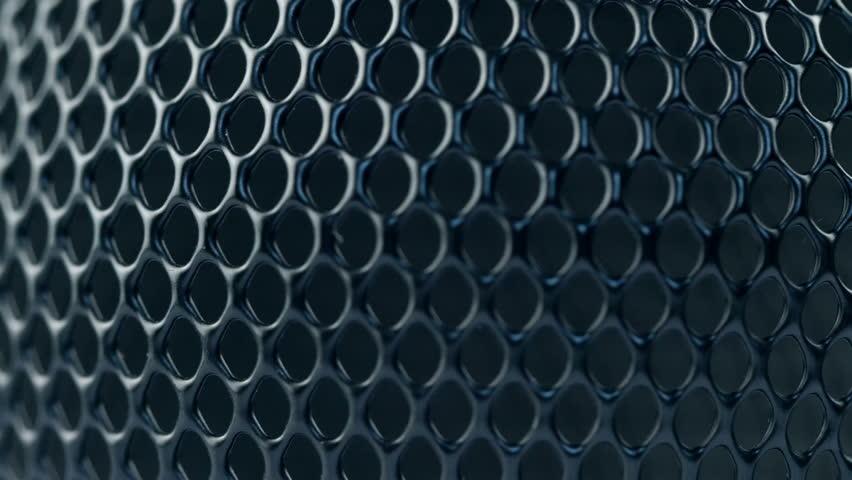 Black metal grid rotating on dark background. Close up macro 4k footage.