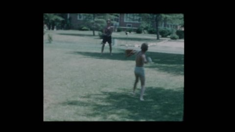 1960 Father and son toss a baseball when antique car drives by