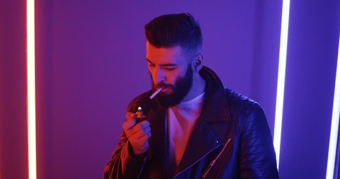 Caucasian stylish good looking man in leather black coat and with beard lighting a cigarette and smoking on the blue and pink neon light wall background.