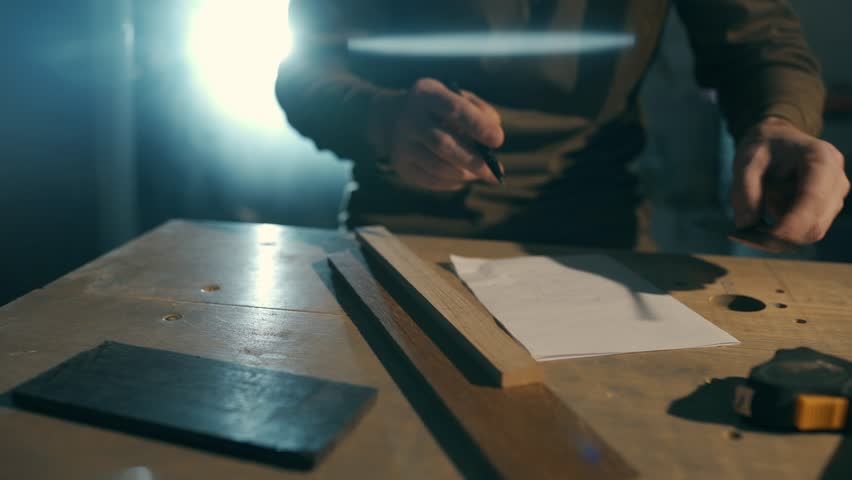 A man is making measurements on a piece of wood. | Shutterstock HD Video #1023252928