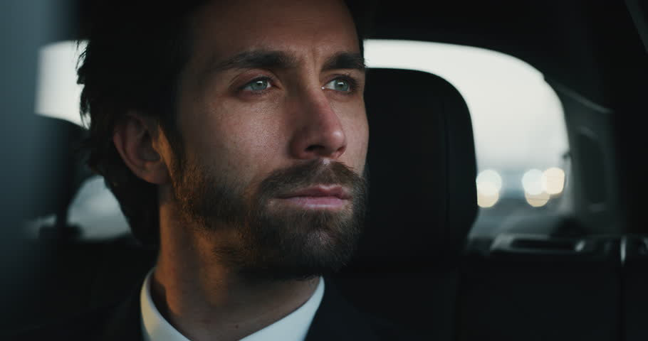 Slow motion close up of young handsome businessman looking outside during traveling in a modern car with a driver in center of the city by day.Shot in 8K.Concept of business,success, traveling luxury  | Shutterstock HD Video #1023373558