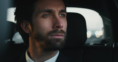 Slow motion close up of young handsome businessman looking outside during traveling in a modern car with a driver in center of the city by day.Shot in 8K.Concept of business,success, traveling luxury