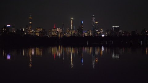Manhattan Skyline and Reflection in Jacqueline Kennedy Onassis Reservoir in Central Park at Night. New York City. United States of America