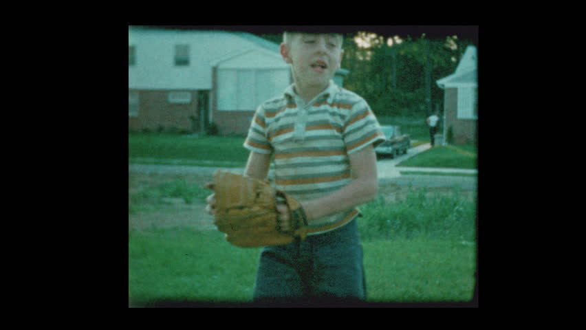 1960 Young blond boy playing catch with baseball in suburban backyard