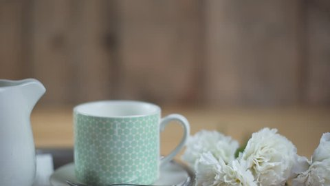Close up of shabby smart romantic white and sky blue cup of milk and coffee cappuccino and milk jug in a tray next to white carnations in a wooden background in comfortable morning breakfast.