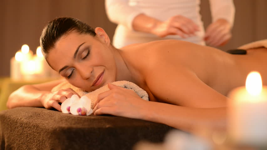 Beautiful Young Woman Receiving Hot Stones Massage At Day Spa. Multiethnic woman relaxing at spa center with a lastone therapy. Portrait of latin girl with eyes closed lying on massage table at salon.
