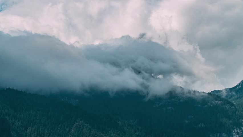 Clouds dodging a mountain top from a far view. | Shutterstock HD Video #1023524998