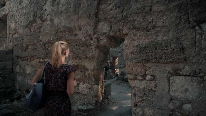Beautyful Woman Walk And Shoot From Mobile In Ancient Town.Young Woman Using Smartphone While Exploring Antique City.Woman In A Dress Walks Along The Ancient Town.Woman Walking In Greek Ancient City.