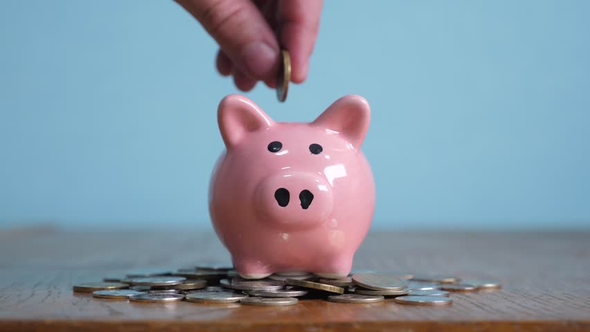 Piggy bank business standing on a pile of coins concept. A hand is putting coin in a piggy bank on a yellow background. saving money is an investment for the future. Banking investment and lifestyle | Shutterstock HD Video #1023549208