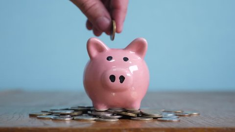piggy bank business standing on a pile of coins concept. A hand is putting coin in a piggy bank on a yellow background. saving money is an investment for the future. Banking investment and lifestyle