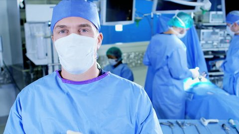 Portrait of male surgeon viewing surgical Health Care hospital Laparoscopy operation carried out by Caucasian male