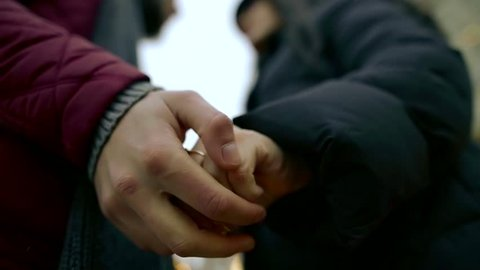 hands of loving pair talking outdoors and stroking palms, close-up tilt-up view