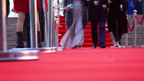 Three people are walking on the red carpet, low angle close up