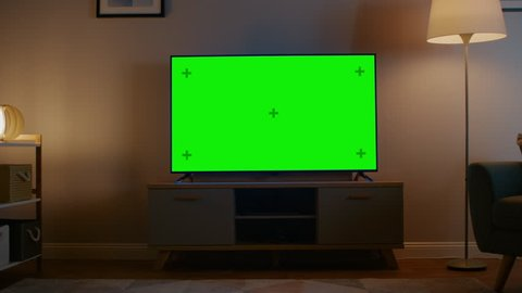 Zoom out shot of a tv with horizontal green screen mock up  cozy evening  living room with a chair and lamps turned on at home