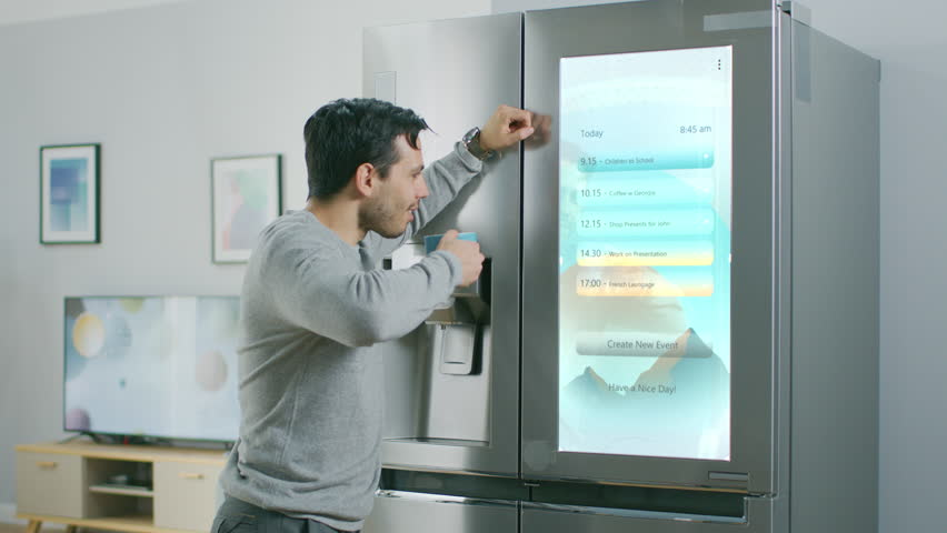 Handsome Young Man Walks Over to a Refrigerator While Drinking His Morning Coffee. He is Checking a To Do List on a Smart Fridge at Home. Kitchen is Bright and Cozy. | Shutterstock HD Video #1023697408