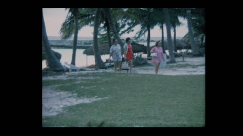 1970 Man smokes cigar with Family on vacation at tropical beach