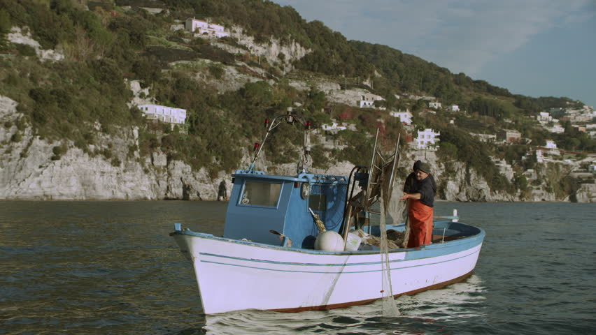 Two busy fishermen sailing on their boat across the sea with view of the Amalfi Coast in the background, on a bright sunny day. Wide shot on 8k helium RED camera.