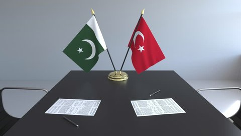 Flags of Pakistan and Turkey and papers on the table. Negotiations and signing an international agreement. Conceptual 3D animation