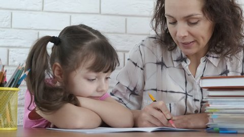 Parent helps the child to do homework. Mother helps daughter to do homework.