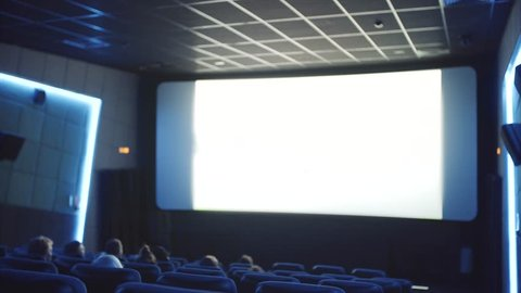 cinema hall with viewers, unidentified film on the screen and staircase between armchairs rows
