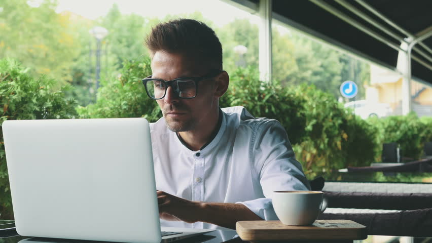 Young businessman dressed in business and glasses sitting in a cafe. | Shutterstock HD Video #1023806398