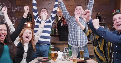 Group of friends are watching a sport game on TV in a vintage pub or restaurant. They all cheer when their favourite team scores