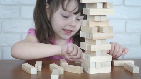 Jenga falls. A child plays wooden puzzles. A little girl pulls out wooden blocks from the tower.