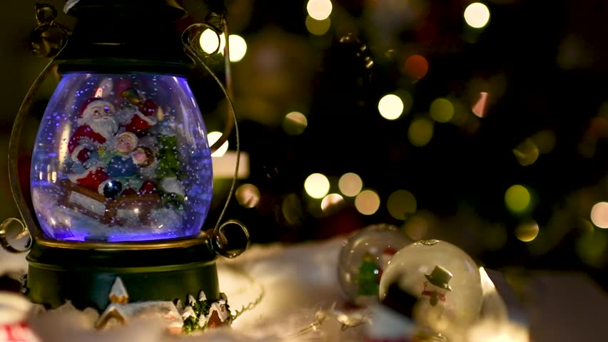 Christmas decoration with snow globes and others beautiful ornamentations on a table and lights blurred in the background. Panoramic plane shift