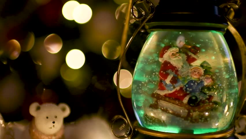 Cute color snow globe with Santa Claus and child on sleigh with Christmas lights blurred in the background. Flat plane