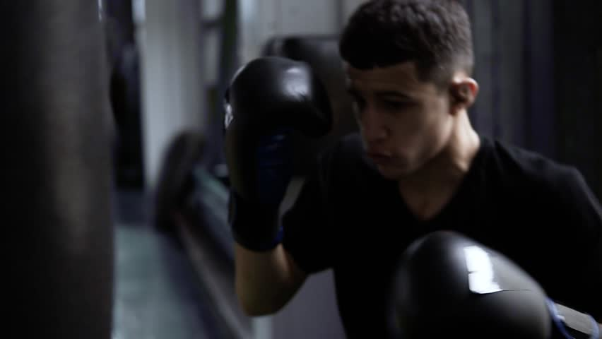 Handhelded footage of young boxer's training. Dark haired man hitting the boxing bag, hard kicks. Motivation in sport. Old style gym, daytime. Close up #1023921658