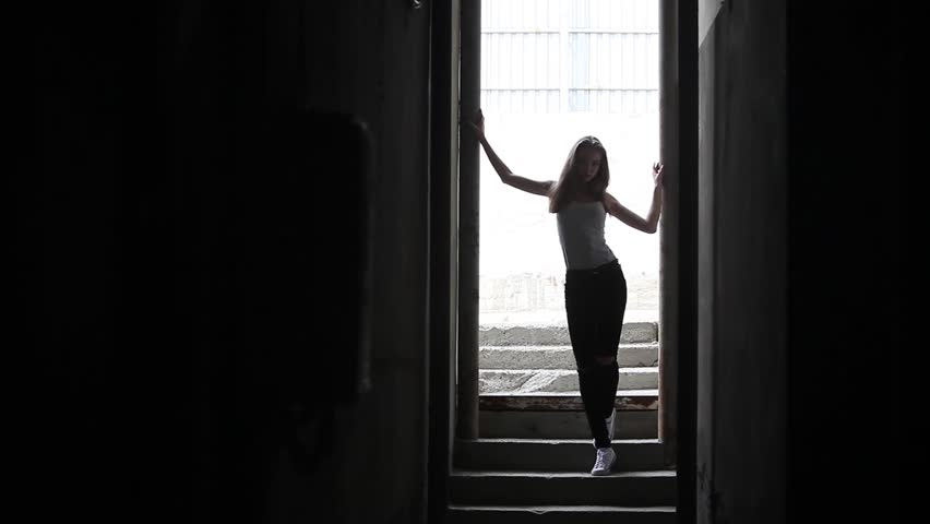 Young woman posing in the shadow of a narrow passage | Shutterstock HD Video #1023938708