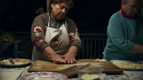 Two focused Italian cooks rolling out dough and forming pillows for gnocchi for cooking. Medium shot on 8k helium RED camera.
