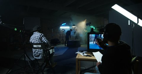 Film crew on stage set while shooting scene with actors fighting in spotlight