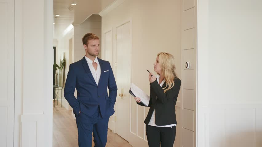 Realtor woman 50s showing a property to young businessman at open house / Selling Real estate  #1023995288