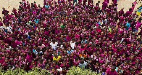 4K close-up aerial static then zoom out view of a rural school with a large group of children gathered on the dirt playround in the Mahenye Village, Zimbabwe