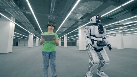 Empty storage unit with a boy in VR-glasses and a moving robot