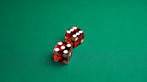 Slow motion two red dice, craps, thrown on green tomentum background, eleven