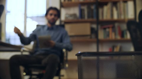 While thinking of ideas, an employee rips and crumples pieces of paper into a ball and throws it at a waste bin in his office. Wide shot on 8k helium RED camera.