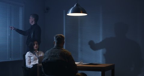 Medium shot of a male and a female investigator interrogating a soldier