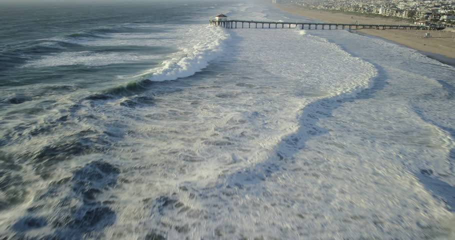 Aerial wide shot of Southern California pier with big waves crashing on the beach and white water tide in the Pacific Ocean from a birds eye view shot in a helicopter.
