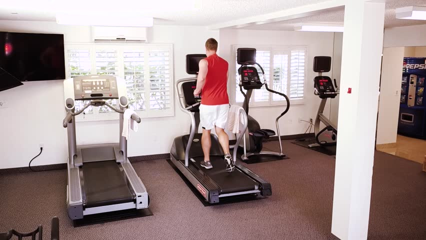 A small view of big sport room where two people are having workout. They are running on elliptical machines. The exercise is intensive. | Shutterstock HD Video #1024082798