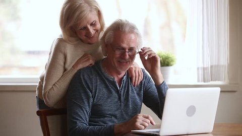 Happy senior middle aged couple laughing talking embracing using laptop together looking at computer screen, smiling older mature family enjoying watching funny video or making online call at home